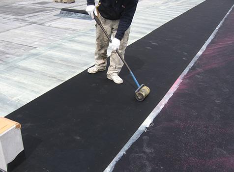 シート防水工事  接着剤塗布後、シートを貼り付け、下地とシートが密着するように転圧作業を行います